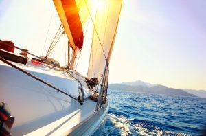 Yacht Sailing against sunset. Sailboat. Yachting. Sailing. Trave